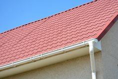 Roof gutter  with house red metal tiled roof. Roof gutter with house red metal tiled roof photo stock images