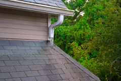 Roof gutter and runoff pipe on a rainy day Stock Image