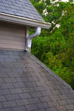 Roof gutter and shingles on a rainy day Royalty Free Stock Photography