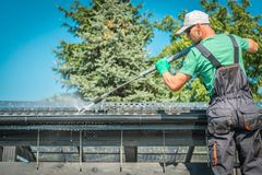 Roof and Gutters Cleaning. Roof and Gutters Power Cleaning Using Pressure Washer. Caucasian Worker stock photography