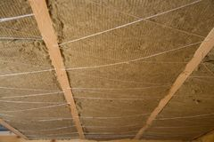 Roof heat isolation with mineral wool in wooden house, building under construction Stock Photos