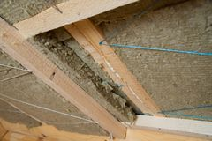 Roof heat isolation with mineral wool in wooden house, building under construction Royalty Free Stock Images