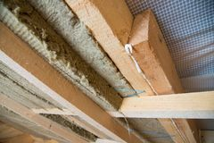 Roof heat isolation with mineral wool in wooden house, building under construction Stock Images