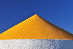 Roof of a hotel, fine arts. Detail of a yellow roof in front of a blue sky royalty free stock photos