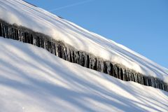 The roof of the house covered with snow and hanging icicles royalty free stock image