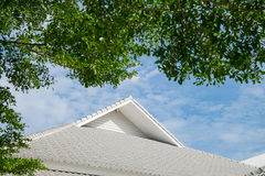 Roof of the house with green tree, blue sky and cloud in vintage. Roof of the house with green tree, blue sky and cloud. building with nature background in Stock Images