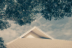 Roof of the house with green tree, blue sky and cloud in vintage. Roof of the house with green tree, blue sky and cloud. building with nature background in Royalty Free Stock Image