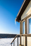 Roof of the house with hanging icicles on blue sky background Royalty Free Stock Photo
