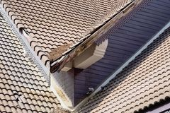 Home roof damage after storm surge. The roof of the house is not very damaged but must be repaired to prevent further damage to the adjacent area royalty free stock photo