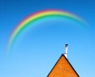 Roof of the house and rainbow. Roof of the house with trumpet and rainbow on blue sky Stock Photos