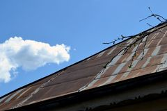 The roof of the House. Rusty roof of blue sky with white clouds stock photo