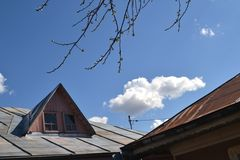 The roof of the house of rusty sheet. Rusty roof of blue sky with white clouds and gazebo at the neighbor's house stock photos