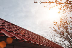 Roof house and the sun. Roof house with tiled roof and the setting sun Stock Photos