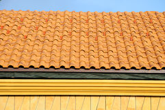 Roof house with tiled roof on blue sky. detail of the tiles and corner mounting on a roof, horizontal. Stock Images