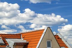 Roof of house with windows and yellow roof tiles Stock Photo