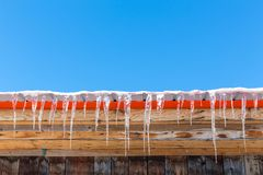 Roof, icicles and blue sky. Icicles hang from a rooftop during a Canadian winter. Blue sky against wooden building with orange paint: comlimentary colours in stock photography
