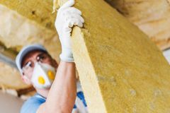 Roof Insulating by Mineral Wool. Caucasian Construction Worker with Piece of Insulating Material, Roof Insulating by Mineral Wool Royalty Free Stock Image
