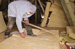 Roof insulation. Worker cutting a piece of ceramic wool for roof insulation Royalty Free Stock Image