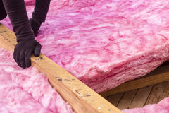 Roof Insulation. Fiberglass roofing insulation being installed stock photography