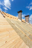 Roof insulation. New wooden house under construction with chimneys against blue sky. Stock Photography