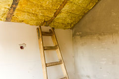 Roof insulation. Old wooden ladder are ready for climbing up to work stock image