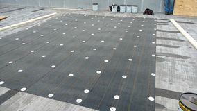 roof leak repairs in progress on Commercial flat roof; roofing Royalty Free Stock Photo