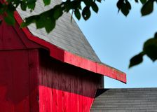 Roof lines on an old red Barn in Hollis NH. Blue azure sunny skies above a black shingled roof on an old red barn in Hillsborough County NH USA stock photos