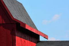 Roof lines on an old red Barn in Hollis NH. Blue azure sunny skies with fluffy cirrus clouds above a black shingled roof on an old red barn in Hillsborough Royalty Free Stock Photo