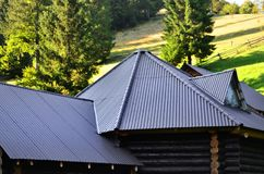 The roof is made of gray embossed metal sheets. Wooden house in the summer fiel. D stock photos