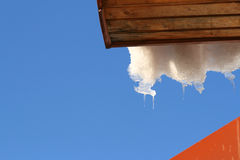 Roof with melting hanging icicles and snow Royalty Free Stock Image