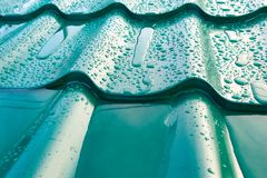 The roof of metal. The green roof of metal with rain drops stock image