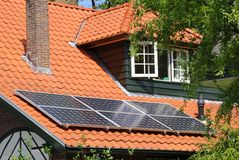 Modern solar panels as an alternative energy source on scenic red tiled roof, Netherlands royalty free stock photos