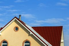 Roof of a new built house with nice window and chimney. Royalty Free Stock Photography