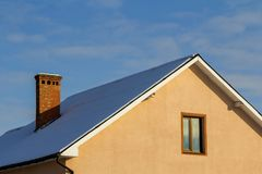 Roof of a new built house with nice window and chimney. Stock Photography