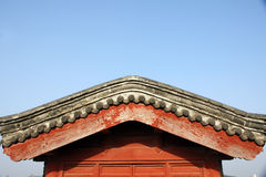 Roof of old Chinese building. Side view of rooftop and brown side of very old Chinese building, blue sky background Royalty Free Stock Photography