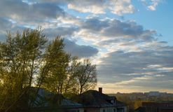 Roof of the old house behind trees against cloudy sky with clouds and sunset Stock Photography