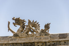 Roof of old house decorated with dragon. Royalty Free Stock Photo