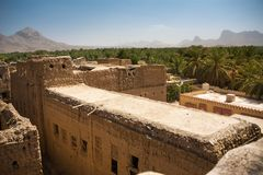 Roof of old mud houses and palm tree in the old village of Al Hamra. Oman stock images