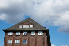 Roof of an old red brick house against a blue sky and clouds in Hamburg Royalty Free Stock Photography