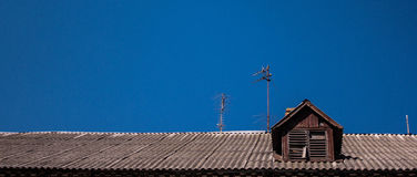 The roof of an old wooden house on a background of pure blue sky Royalty Free Stock Photos