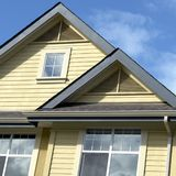 Roof Peaks. New construction with beige siding,brown roof and wood trimmed windows Stock Photography