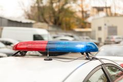 Roof of a police patrol car with flashing blue and red  lights, sirens and antennas.  Stock Photos
