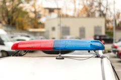 Roof of a police patrol car with flashing blue and red  lights, sirens and antennas.  Stock Photo
