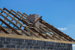 Roof rafters. A new build roof with a wooden truss framework making an apex against a blue sky with cloud stock photos