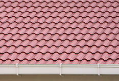 Roof and rain gutter. Red roof made of metal with rain gutter installed Royalty Free Stock Photos