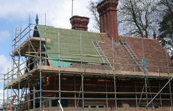 Roof repair. Roof tiles being replaced, repaired. Scaffold Stock Photography