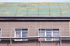 Roof repair construction and scaffold near windows Stock Photo