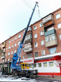 Roof repair a five-story brick home with a crane in the city of Omsk Stock Images
