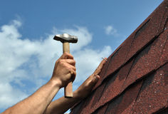 Roof repair. Hand with a hammer to drive a nail, roof repairs. Bitumen Roof Asphalt Shingles Royalty Free Stock Photos