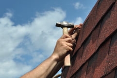 Roof repair. Hand with a hammer to drive a nail, roof repairs. Bitumen Roof Asphalt Shingles Stock Photo